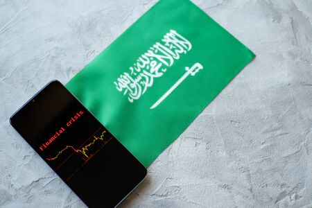 The economic crisis, the news and the schedule drop-down on the smartphone screen. The financial crisis in Saudi Arabia. Flag Imagens