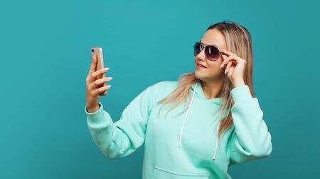 Stylish trendy hipster girl in the blue hoodie with the hood uses a smartphone. Happy young blonde enjoys social networking and a good app