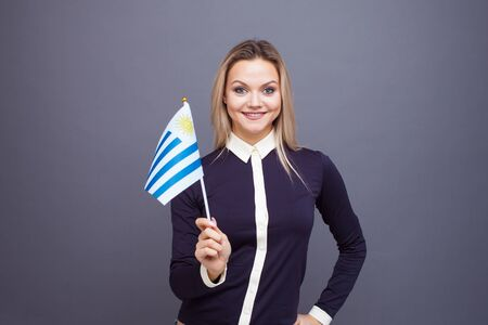 Immigration and the study of foreign languages, concept. A young smiling woman with a Uruguay flag in her hand. Girl waving a Uruguayan flag on a gray background Foto de archivo