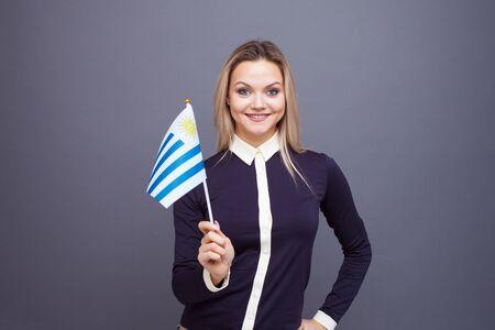 Einwanderung und das Studium von Fremdsprachen, Konzept. Eine junge lächelnde Frau mit einer Uruguay-Flagge in der Hand. Mädchen schwenkt eine uruguayische Flagge auf grauem Hintergrund Standard-Bild