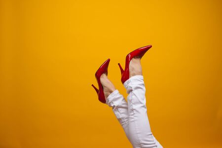 Female feet in beautiful red stiletto shoes, yellow background copy space. Women's fashion, clothing and shoes