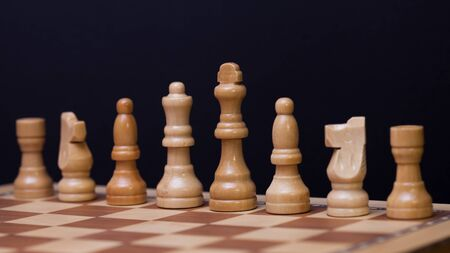 Wooden chess in a contrasting light. A game of chess, an intellectual competition, a concept of strategy and long-term planning. White figure