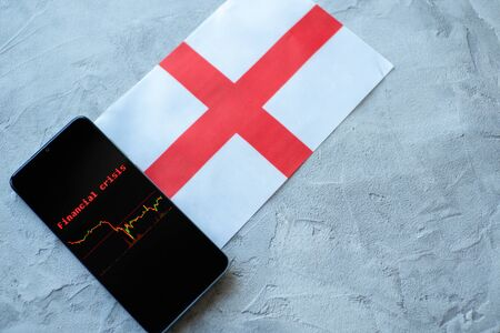 The economic crisis, the news and the schedule drop-down on the smartphone screen. The financial crisis in England. Flag