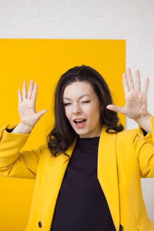 Young positive woman in yellow, bright portrait on a yellow background. Funny girl dancing, vertical background with frame