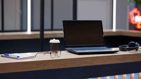 Workplace with a laptop, Notepad and pen, in the distance are headphones and a cardboard coffee Cup, Desk for work, glasses on the table