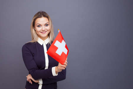 Immigration and the study of foreign languages, concept. A young smiling woman with a Switzerland flag in her hand. Girl waving a Swiss flag on a gray background