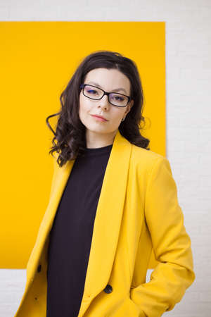 Stylish young woman in a yellow jacket on a yellow background, bright and trendy portrait