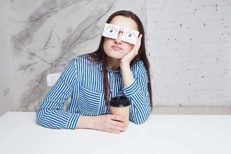 Drowsiness and procrastination. A student pretends to work, a girl in glasses with stickers with a pattern of open eyes