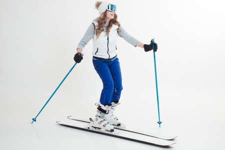 Skier maneuvers on mountain skis, photos on a white background in the Studio, winter sports, Hobbies and a healthy lifestyle. Young woman on skis in light winter clothing for outdoor activities Foto de archivo