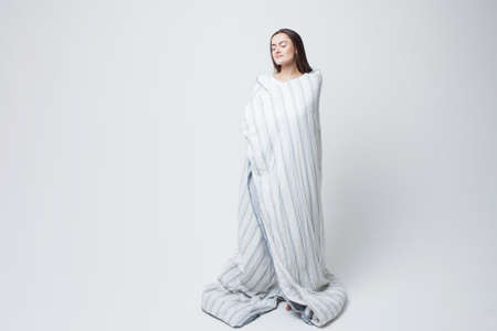 Healthy sleep and drowsiness, beautiful young woman standing wrapped in a blanket, light gray background.