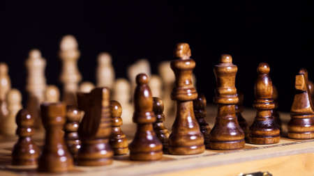 Wooden chess in a contrasting light. A game of chess, an intellectual competition, a concept of strategy and long-term planning. Black figure