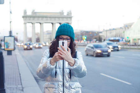 A woman in a down jacket and a hat walks around the city and takes photos on a smartphone, autumn-winter, traveling around the city