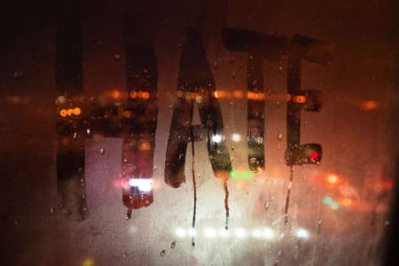 Hate, negative emotions. Inscription on the fogged glass, night city on the background. image with tinting and noise effect
