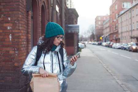 courier or volunteer carries food in a paper bag. A young woman in a warm jacket holds a parcel and uses a smartphone