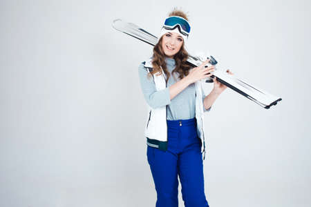 Smiling woman skier in a hat and mask for skiing. A young woman in clothes for skiing and outdoor activities. A woman holds skis and poses on a white background in the Studio.