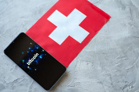 Cryptocurrency and government regulation, concept. Modern economy, smartphone with bitcoin sign on the screen on the background of the flag of Switzerland