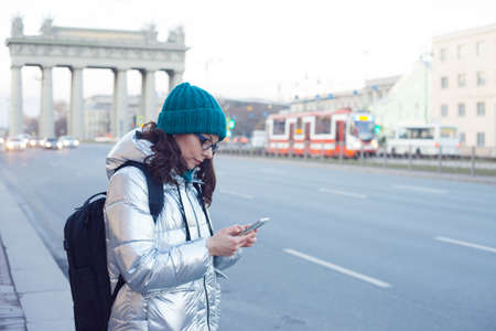 woman in a down jacket and hat stands at a public transport stop and uses a smartphone. Communication in messengers and social networks, mobile Internet