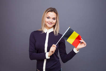 Immigration and the study of foreign languages, concept. A young smiling woman with a Belgium flag in her hand. woman waving a Belgian flag on a gray background