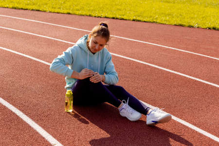 Sports injuries, a young female athlete kneads her knee, sprains or muscles. Runner in a blue hoodie on a street treadmill