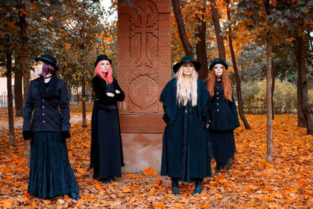 Coven of witches, a group of different friends as witches meet Halloween. Young women in black clothes and hats