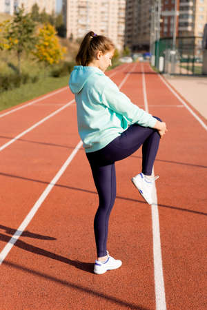 Training on the street, a young female athlete makes a workout on the street platform. Female athlete warms up before training on a treadmill, stretching on a rubber stadium
