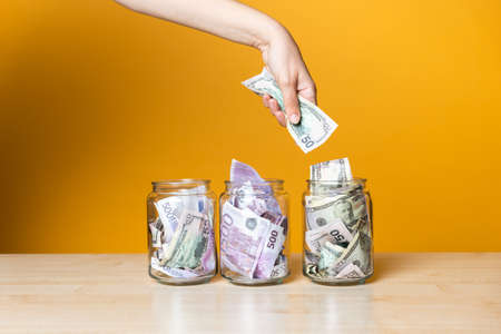 Multi-currency accounts, concept. Dollars and euros in a glass jar on a bright yellow background. Investment and increase of personal finances. The hand takes or puts the banknotes in one of the cans