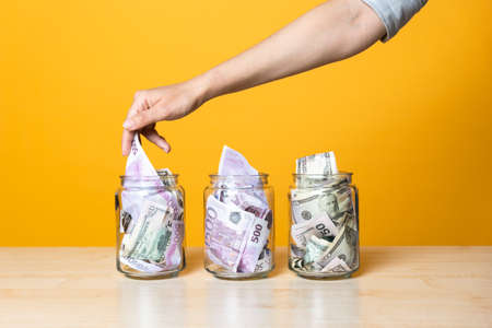 Multi-currency accounts, concept. Dollars and euros in a glass jar on a bright yellow background. Investment and increase of personal finances. The hand takes or puts the banknotes in one of the cans Banque d'images