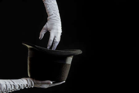 Hand gestures. illusionist holds a hat in his hands and shows magic and tricks. Black background Banque d'images