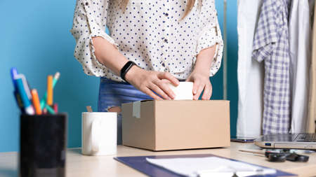 Small business, young female entrepreneur at the table packing a small box of goods, parcel for online store customers. Workplace, portrait on a blue background