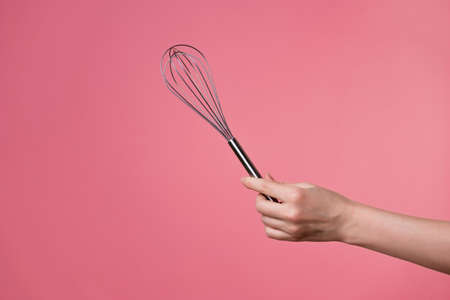 Whisk for whipping cream, making desserts. A womans hand and kitchen tools. pastry chef on a pink background.