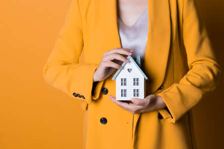 Take a mortgage, lending for the purchase of real estate. A young woman with a small house in her hands on a bright yellow background. Financial goals for the family, the purchase of their home.