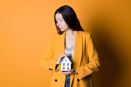 Real estate insurance, taking care of your home and family, concept. Financial and investment instruments. woman in yellow on yellow background holds house in her hands, covering it with her hand.