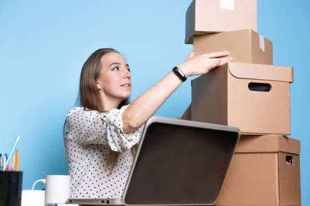 Small business, young female entrepreneur working at a Desk, using a laptop for work, managing an online store and communicating with customers. a stack of cardboard boxes is ready for delivery
