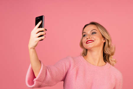 young woman in pink on a pink background takes a selfie on her phone,