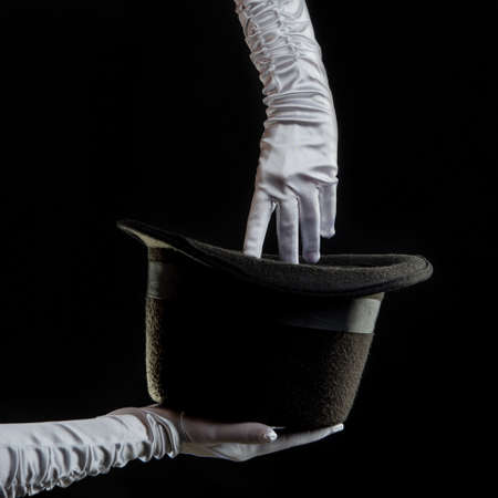 Hand gestures. Showman shows disappearing tricks in a hat, white gloves and black top hat,