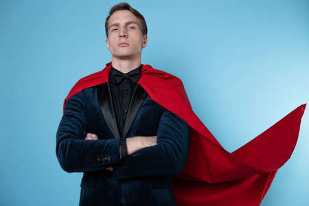 charismatic and successful business hero. A young man in a suit and a red cape,