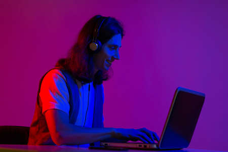 Funny guy gamer playing on a laptop. A young man with headphones