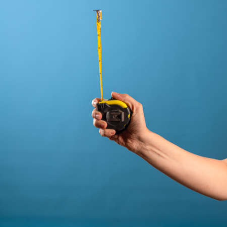 Measure it, a yellow construction tape measure to measure the length of something. Roulette with a measured segment in a female hand, blue background