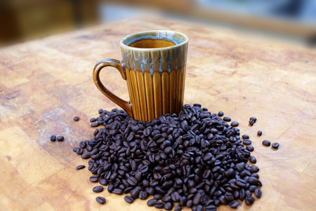 vintage coffee cup with coffee beans on butcher block