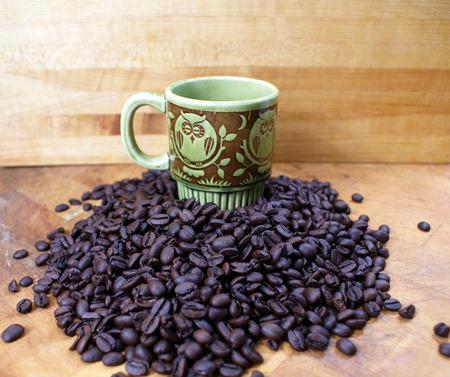 vintage owl coffee cup with pile of coffee beans Zdjęcie Seryjne