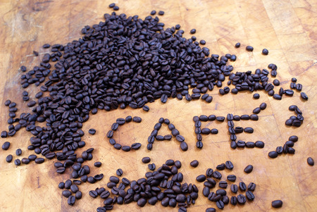 spelled: cafe spelled out in coffee beans at angle on butcher block