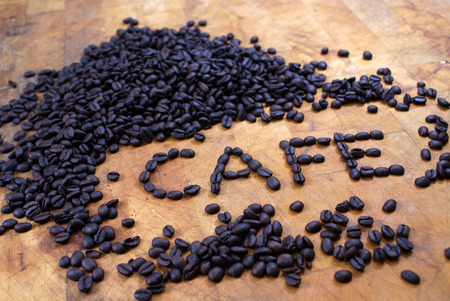 spelled: dark cafe spelled out in coffee beans on butcher block
