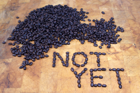 not yet spelled in coffee beans on butcher block