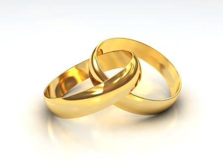 anillos de boda: Un par de anillos de boda de oro sobre fondo blanco Foto de archivo