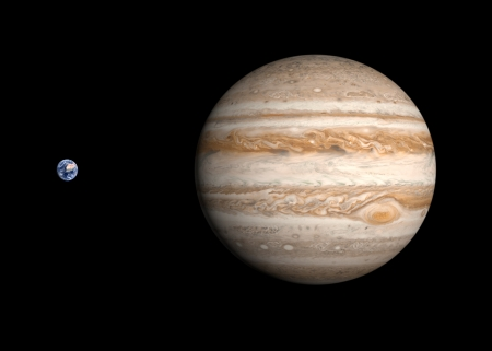 jupiter: A comparison between the planets Earth and Jupiter on a clean black background. Stock Photo