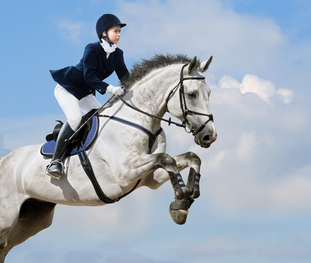 Young girl jumping with gray horse 스톡 콘텐츠