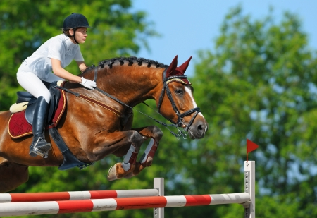 woman and horse: Young woman jumping with bay horse