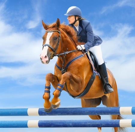 springpaard: Paardensport - Toon springen (jonge vrouw en zuring hengst) op de achtergrond van de hemel Stockfoto