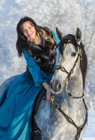 dapple horse: Woman in a blue dress riding on a grey Spanish horse