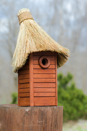 Nesting box. Wooden nest box handmade with thatched roof. Wooden house for birds